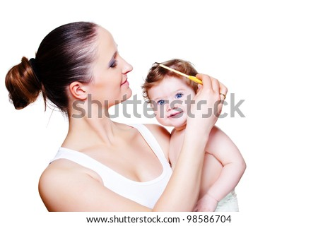 Loving mother combing baby hair - stock photo