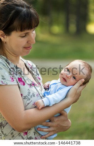 Loving mother hand holding cute little newborn baby child walking outdoor - stock photo