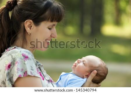 Loving mother hand holding cute sleeping newborn baby child - stock photo