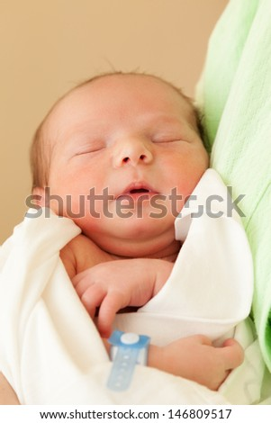 Loving mother hand holding cute sleeping newborn baby child