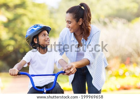 loving mother help her cute son ride a bicycle - stock photo