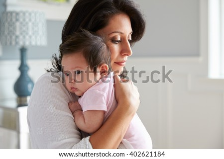 Loving Mother Holding Baby Daughter At Home - stock photo