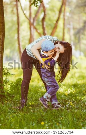 Loving mother kissing her son - stock photo