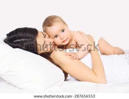 Loving mother lying with cute baby together on the bed at home