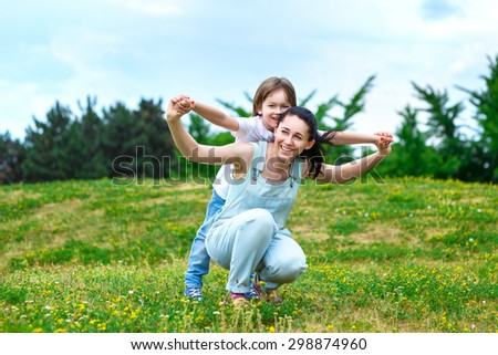 Loving mother rolls on a back of small son in park. They playing fun game. - stock photo