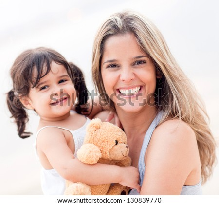 Loving mother with her child smiling outdoors - stock photo