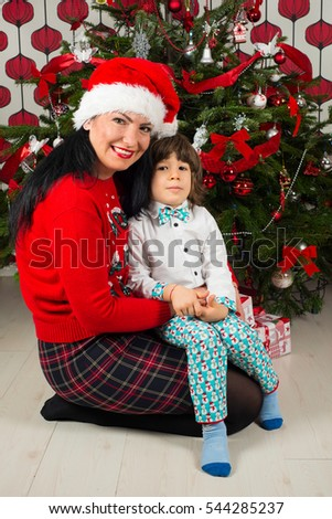 Loving mother with her son sitting in front of Christmas tree
