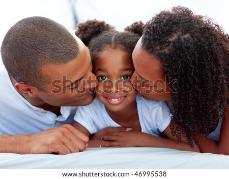 Loving parents kissing their daughter lying on a bed - stock photo