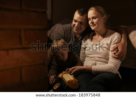 Loving parents sitting arm in arm near the fireplace playing with their young son and his colorful yellow plastic toy truck as the toddler sits on their laps - stock photo