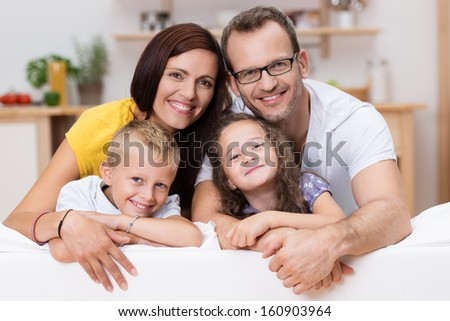 Loving parents with their little son and daughter posing together for a portrait leaning over the back of a large sofa in the living room - stock photo