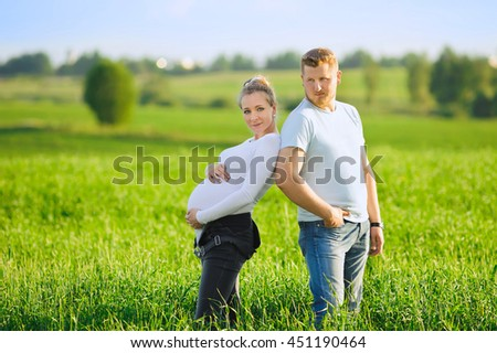 Loving pregnant couple in field at sunset, Young parents expecting a little baby,