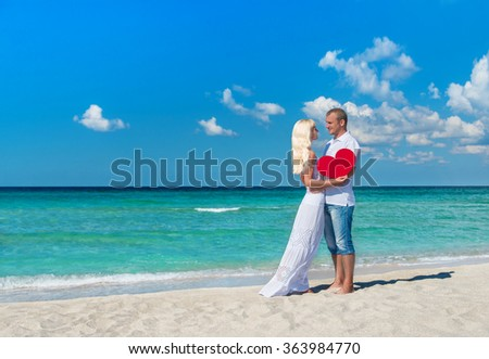 Loving romantic hug couple at sunny ocean beach with red heart symbol - St.Valentines Day travel concept - stock photo