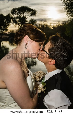 Loving same sex married couple kissing near lake - stock photo