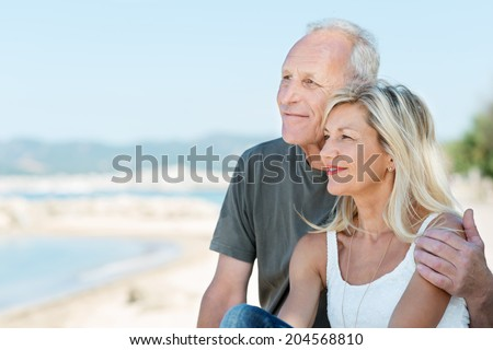 Loving senior couple at the beach sitting arm in arm smiling as they gaze out over the ocean enjoying the summer sun - stock photo