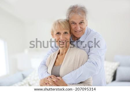 Loving senior couple looking at camera - stock photo
