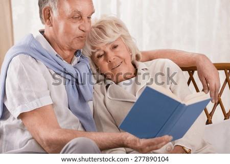 Loving senior couple reading together interesting book - stock photo