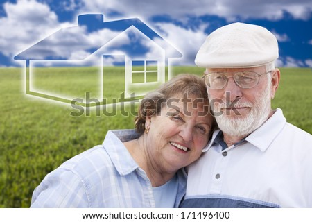Loving Senior Couple Standing in Grass Field with Ghosted House on the Horizon. - stock photo