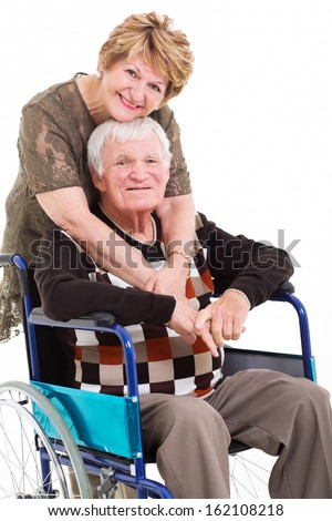 loving senior wife hugging disabled husband on white background - stock photo
