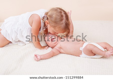 Loving sister kissing her small baby brother - stock photo