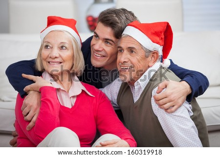 Loving son with parents wearing Santa hats looking away at home - stock photo