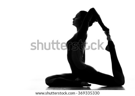Loving sport. Silhouette of a flexible sporty woman practicing yoga indoors isolated on white