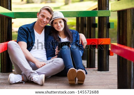 loving teen couple with tablet computer sitting on bridge outdoors - stock photo