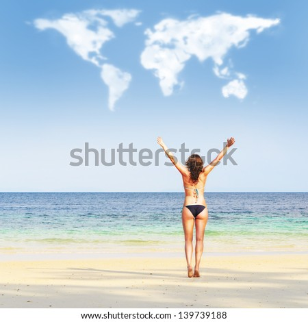 loving travelling. young woman on beach is trying to embrace continents shaped clouds