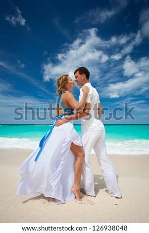 Loving wedding couple on beach in white dresses - stock photo