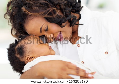 loving young african mother holding her sleeping baby daughter at home - stock photo