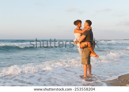 Loving young couple at the beach , in a late summer hazy day at dusk, wearing  a white dress and shorts, enjoying, going barefoot in the ocean water, getting wet, teasing and kissing one another.