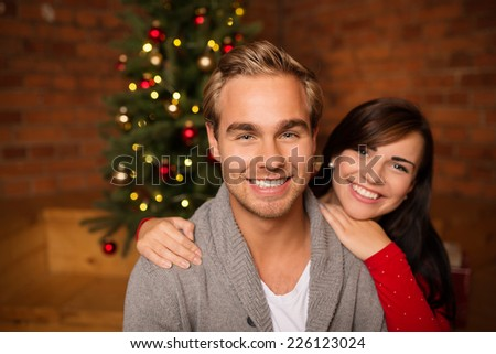 Loving young couple celebrating Christmas standing in front of a decorated tree in a close embrace smiling at the camera - stock photo