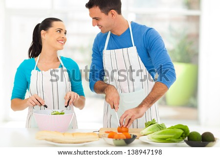 loving young couple chatting while preparing salad together at home - stock photo