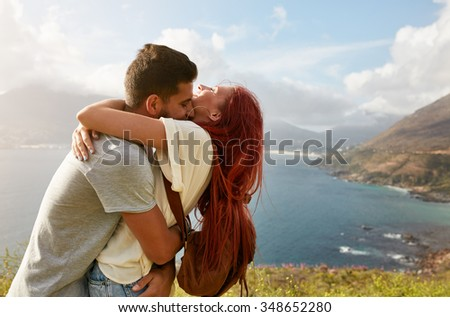 Loving young couple embracing and kissing on a summer day outdoors. Man hugging his girlfriend. Enjoying their summer vacation. - stock photo