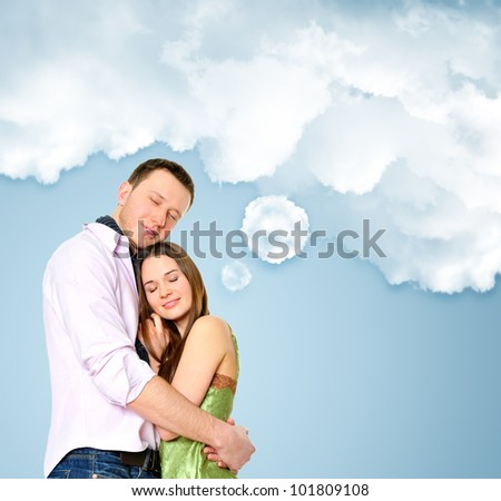 Loving young couple embracing. Blank cloud with their thoughts for your text - stock photo