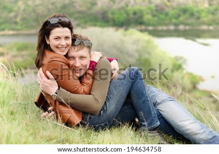 Loving young couple embracing on a hill top lying in the grass in each others arms smiling happily at the camera with a scenic river valley below