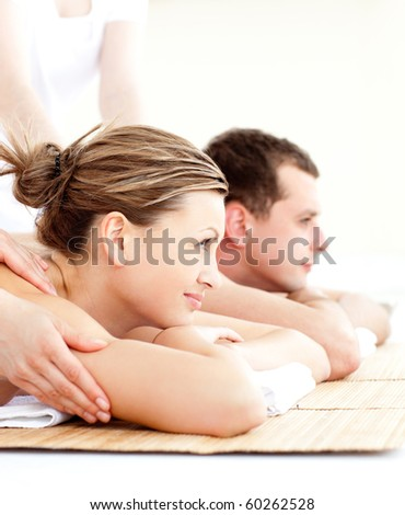 Loving young couple enjoying a back massage in a spa center