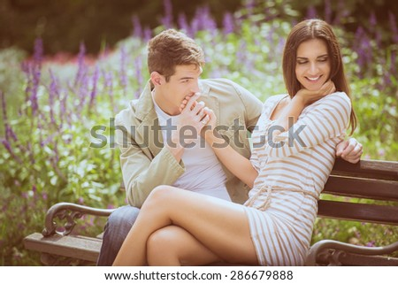 Loving young couple flirting while sitting at a park bench. - stock photo
