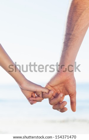 Loving young couple holding hands on the beach