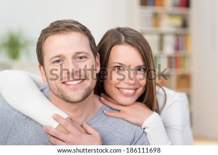 Loving young couple in an intimate embrace sitting together in their living room smiling at the camera - stock photo