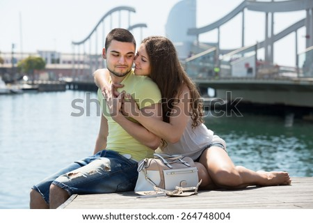 Loving young couple in shorts resting on the berth in port at summer day