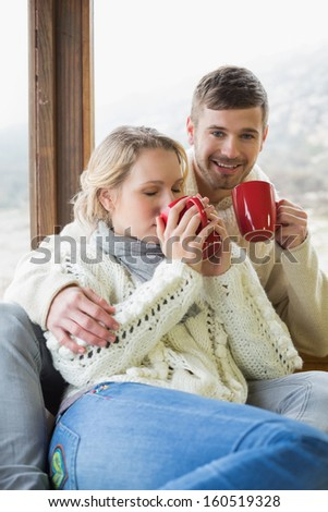 Loving young couple in winter clothing drinking coffee against cabin window