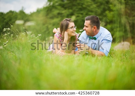 Loving young couple looking at each other and smiling while relaxing in park - stock photo