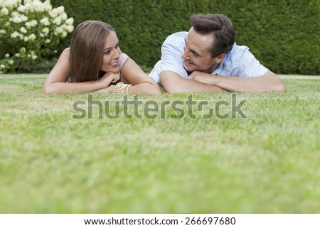 Loving young couple looking at each other while relaxing in park - stock photo