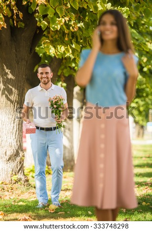 Loving young couple on a date with flowers and with a gift in the park