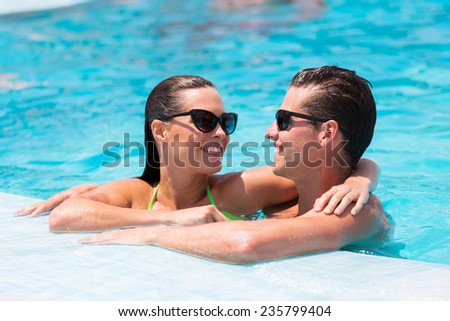loving young couple relaxing in swimming pool - stock photo
