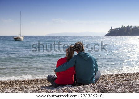 Loving young couple sitting on the white sand by sea, and enjoying each other , on windy sunny day, high, rough sea with sailboat  and bright blue sky in the background - stock photo