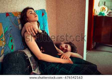 Loving young couple sleeping on the couch hugging each other. The concept of rest, fatigue