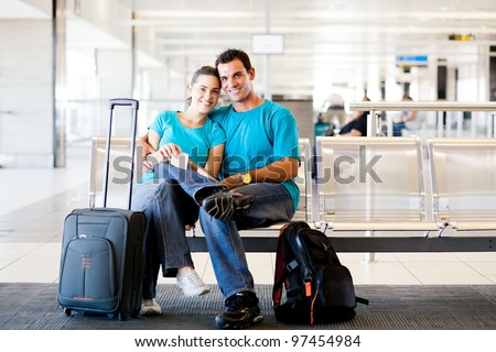 loving young couple waiting for flight at airport - stock photo