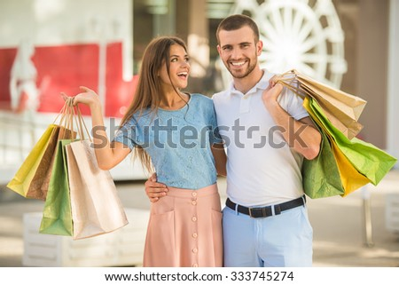 Loving young couple with bags for shopping, walk to town - stock photo