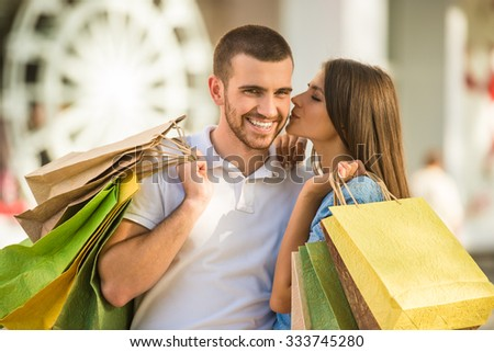 Loving young couple with bags for shopping, walk to town